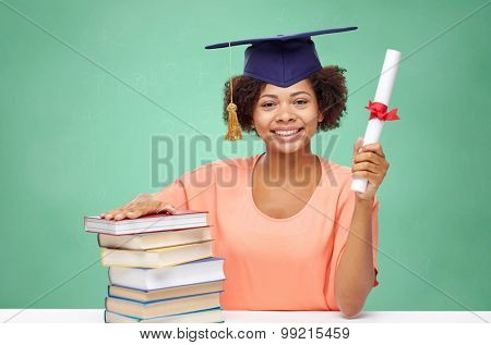 education, school, knowledge, graduation and people concept - happy smiling african american student girl in bachelor cap with books and diploma over green chalk board background