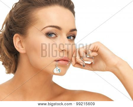 beautiful woman holding shiny diamond necklace in mouth