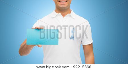 medicine, health care, gesture and people concept - close up of middle aged man in t-shirt with sky blue prostate cancer awareness ribbon holding blank paper card