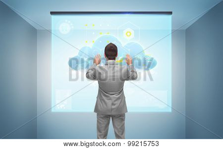 business, people, technology and cloud computing concept - businessman working with virtual screen over gray room background from back