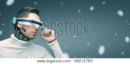people, technology, future and progress - man with futuristic 3d glasses and microchip implant or sensors over gray background and highlights
