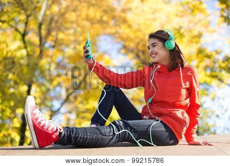 technology, lifestyle and people concept - smiling young woman or teenage girl with smartphone and headphones listening to music outdoors over autumn park background