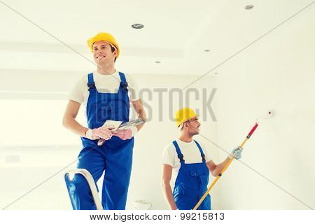 business, building, teamwork and people concept - group of smiling builders in hardhats with plastering tools indoors