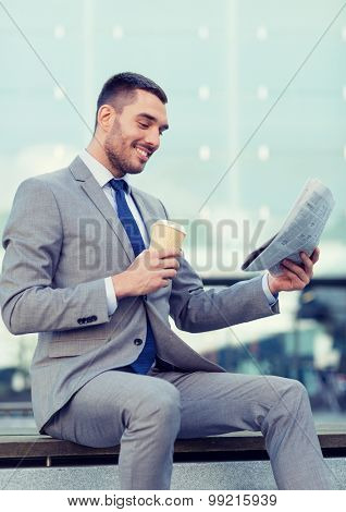 business, hot drinks and people and concept - young smiling businessman with paper coffee cup and newspaper over office building
