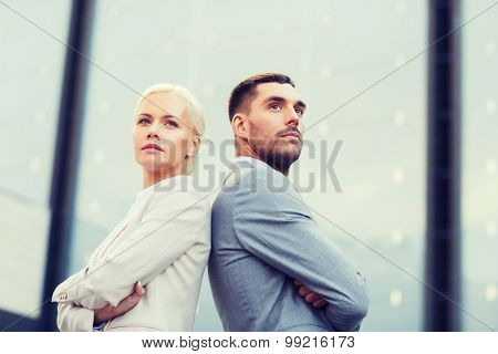 business, partnership, success and people concept - businessman and businesswoman standing over office building
