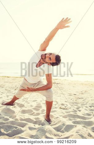 fitness, sport, people and lifestyle concept - smiling man making yoga exercises on beach
