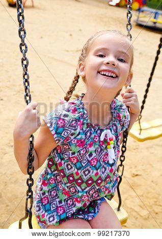 Smiling Little Girl Having Fun On A Swing In The Park