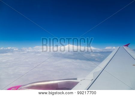 Blue horizon with clouds, aerial shot from airplane, with wing visible