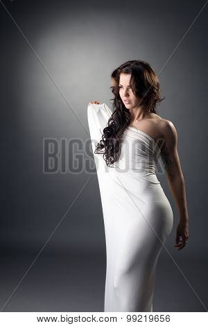 Seductive brunette posing in loose-fitting dress