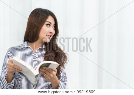Young Asian Woman Relaxing In Her Living Room Reading Book At Home
