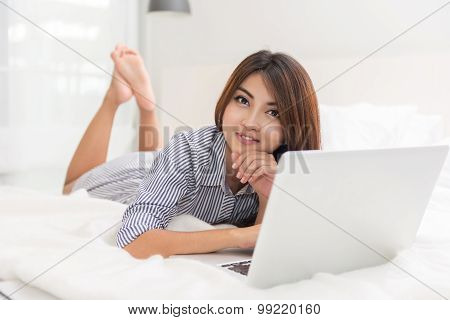 Portrait of beautiful happy young asian woman Working on the bed