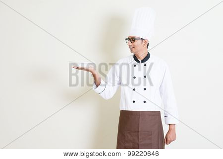 Portrait of handsome Indian male chef in uniform presenting an empty dish and smiling, standing on plain background with shadow, copy space.