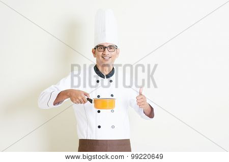 Portrait of handsome Indian male chef in uniform cooking food and thumb up, standing on plain background with shadow, copy space on side.