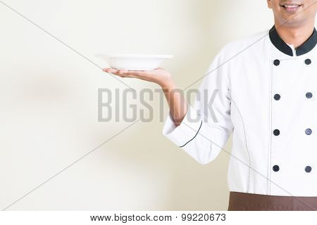 Portrait of Indian male chef in uniform presenting an empty dish, standing on plain background with shadow, copy space.