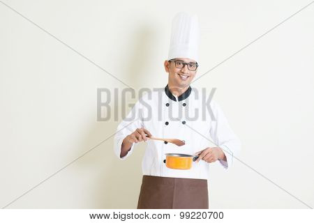 Portrait of handsome Indian male chef in uniform holding cooking pot and stirring food, standing on plain background with shadow, copy space on side.