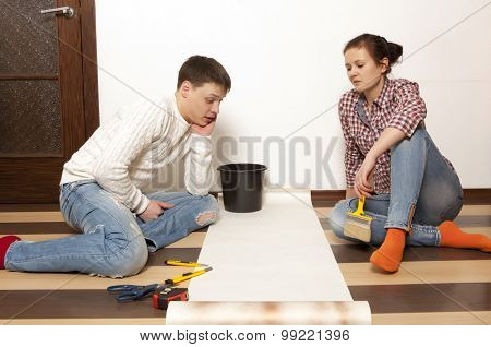 Couple putting new wallpaper in room. Repair, building and home concept