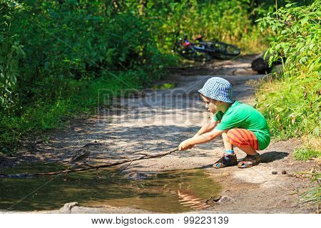 little boy playing with a stick in water puddle outdoors