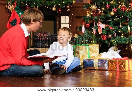 father and son reading book by fireplace