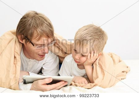 father and son looking at touch pad in bedroom