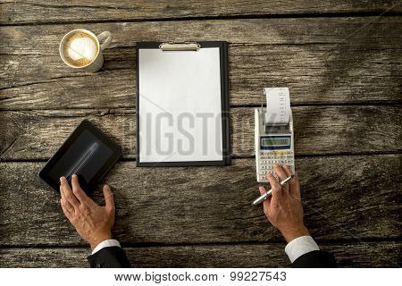 Businessman With Devices And Paper On Table