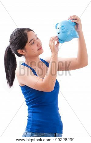 Happy woman holding pink piggy bank on white background