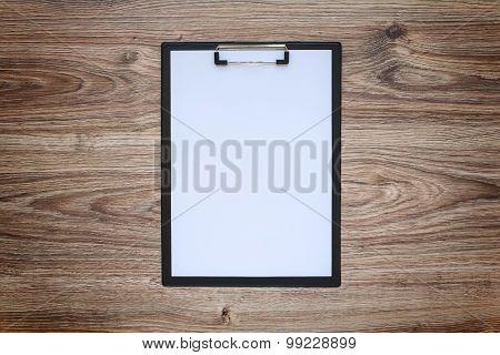 blank paper in clipboard on wooden table