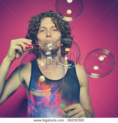 Young man blowing soap bubbles, studio pink background, image toned.