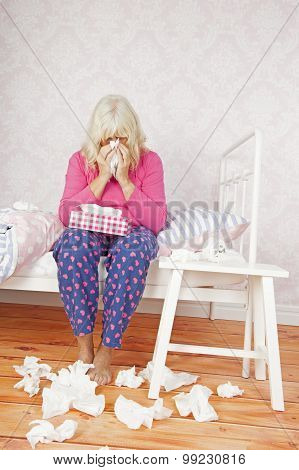 Woman Sitting On Bed With Tissues