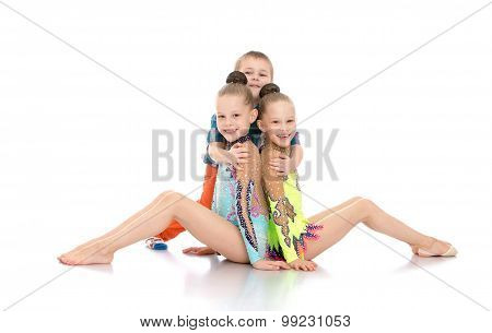 Boy hugging girls gymnasts