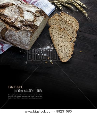 Rustic Bread Loaf And Slices On Dark Wood Fading To Black, Sample Text Bread Is The Staff Of Live