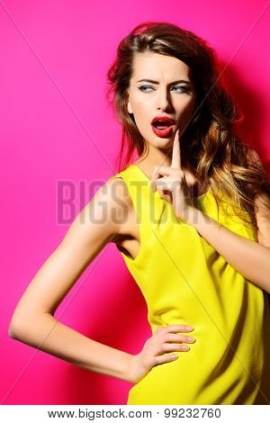 Beautiful fashion model in bright yellow dress posing with her long hair. Beauty, fashion concept. Hair, healthy hair.