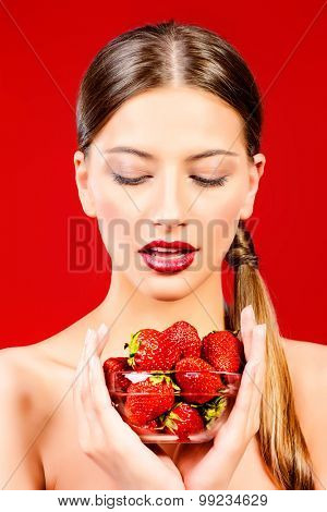 Attractive young woman eating fresh strawberry. Sexual lips, red lipstick. Healthy food concept. Red background.