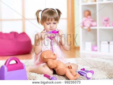 Kid girl playing the doctor with her newborn baby doll in room