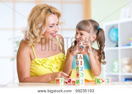 Smiling mother assisting girl in playing block game