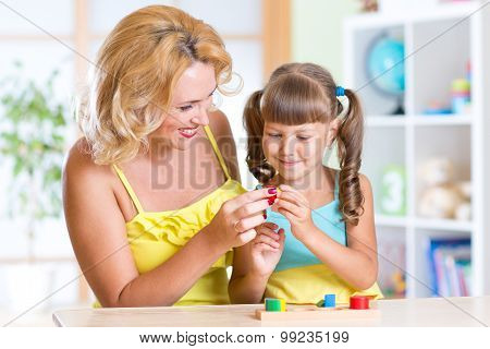 child with mother playing together at table