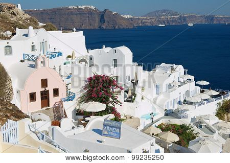 View to hotels buildings with a sea view to volcanic caldera in Oia, Greece.