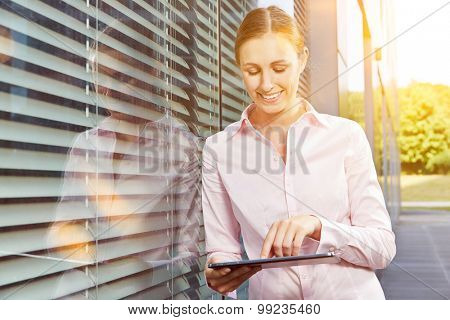 Smilying young business woman with tablet computer in summer on a sunny day