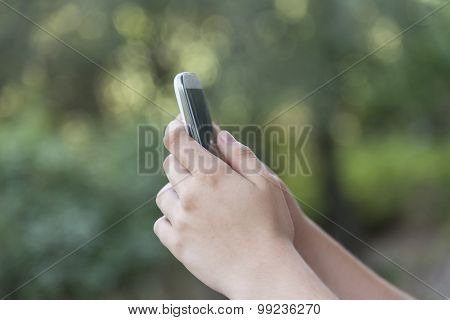 Teenage girl using mobile smart phone, focus on hands