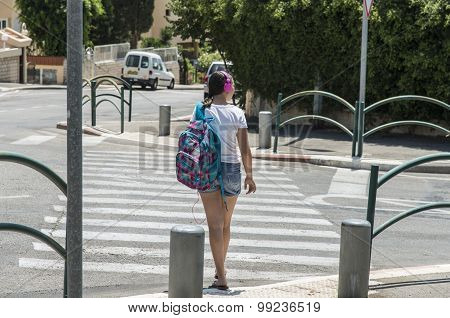 Teenage school girl with a backpack on her back and headphones. back view
