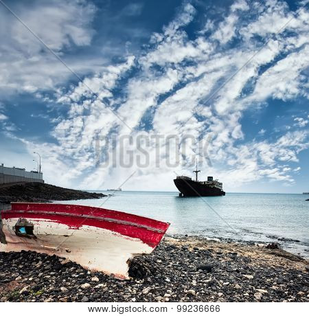 boat on the backgrond with old broken agrounded ship against sky , Lanzarote, Canary Islands, Spain