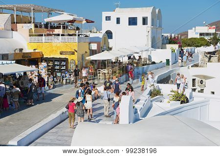 Tourists walk by the street in Oia, Greece.