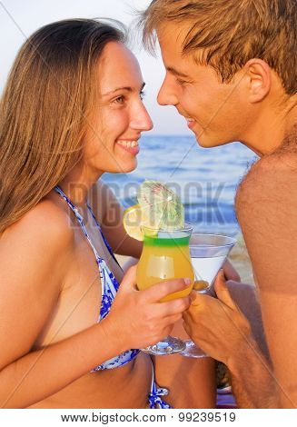 Couple Drinking Tropical Cocktails On The Beach