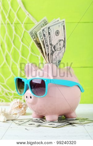 Pink Piggy Bank With Glasses On White Wooden Background