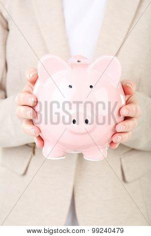 Female Hand Holding Pink Piggy Bank