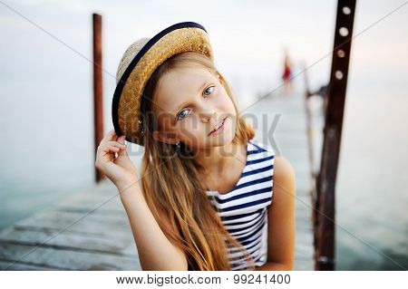 Girl In Striped Vest And A Straw Hat Against The Sea