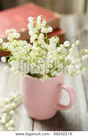 Lily Of The Valley In Cup On Grey Wooden Background