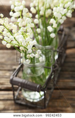 Lily Of The Valley In Bottles On Brown Wooden Background