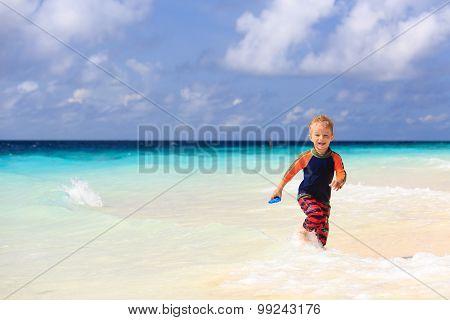 little boy running on sand tropical beach