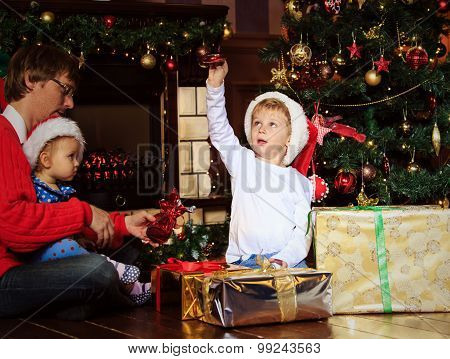 father and kids with presents in christmas