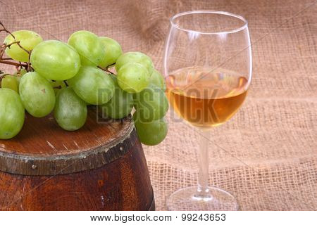 wooden barrel with glass of wine and grapes